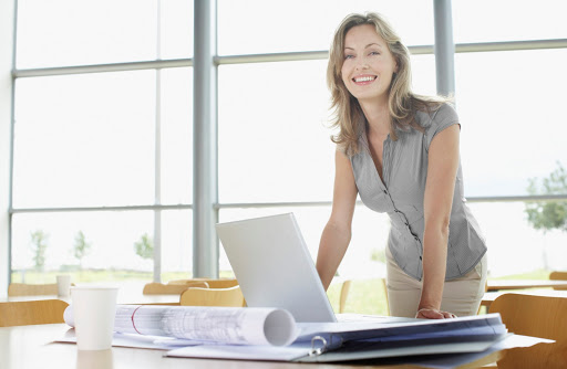 Businesswoman at desk with blueprints and laptop